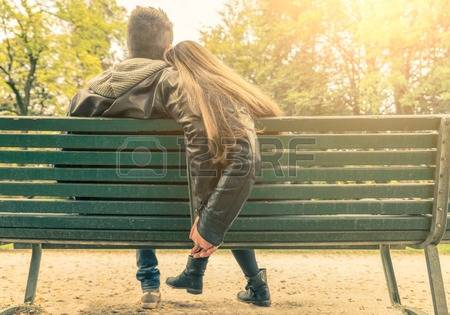 32762345-couple-on-a-bench-two-lovers-sitting-on-a-bench-in-a-park-and-holding-themselves-by-hands-concepts